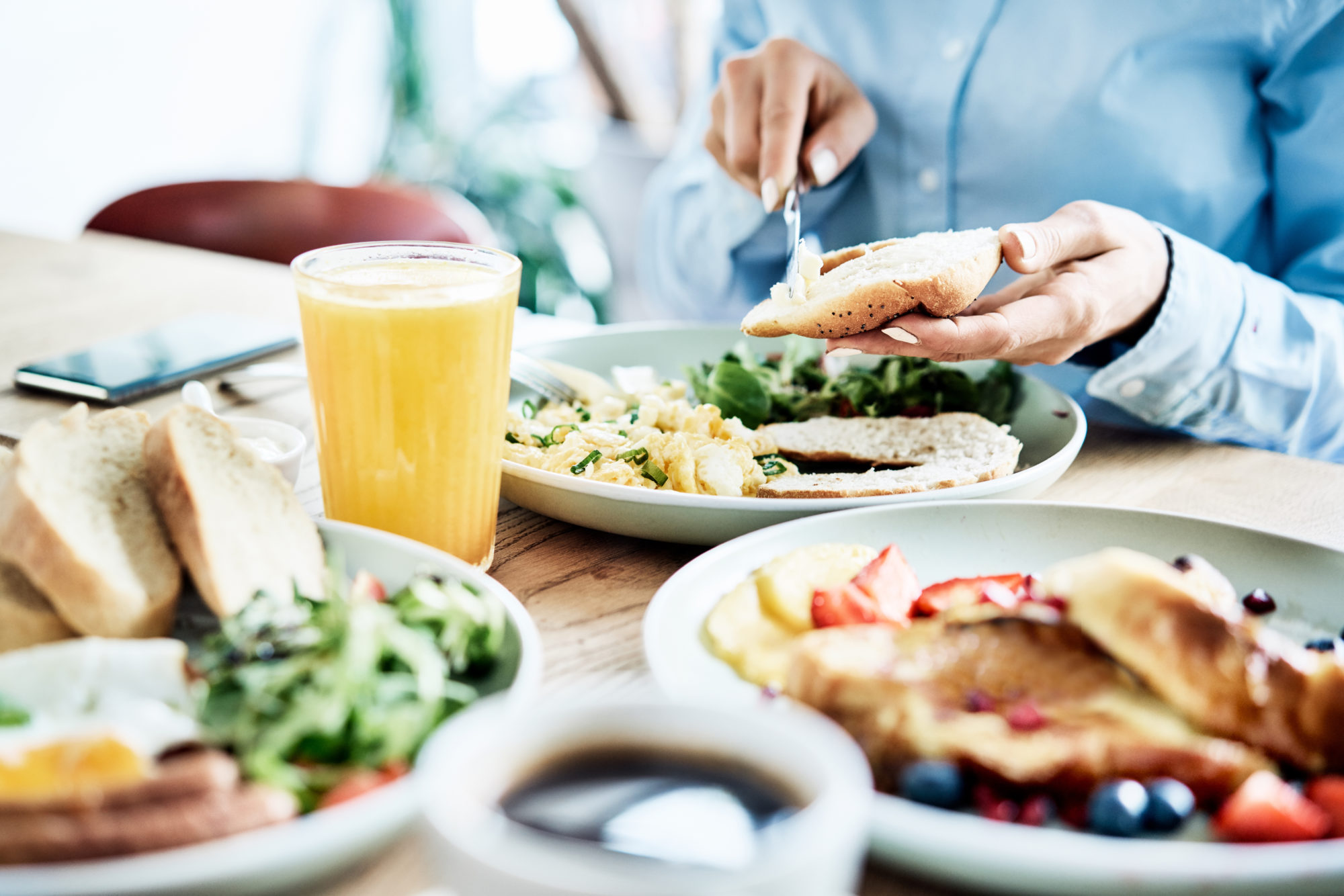 Woman having delicious and healthy breakfast in restaurant. Close up of nutritious food